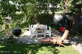 Perceel van 300 m2, omheinde tuin, twee schommels, schommelstoel, Tuin met royale tafel, ook onderrijdbaar voor mindervaliden, barbeque.