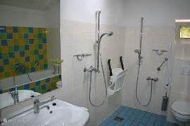 Ruime badkamer, ook aangepast voor mindervaliden of ouderen, met hoger toilet met steunen, douchestoel, in hoogte verstelbare wastafel, 2 douches, ligbad met steunen.