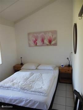 De grote slaapkamer met bed 140x200 en synthetische dekbedden en kussens.  Een kledingkast en een kleine TV.
