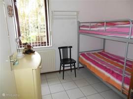 De kinder slaapkamer met stapelbed en legkast.