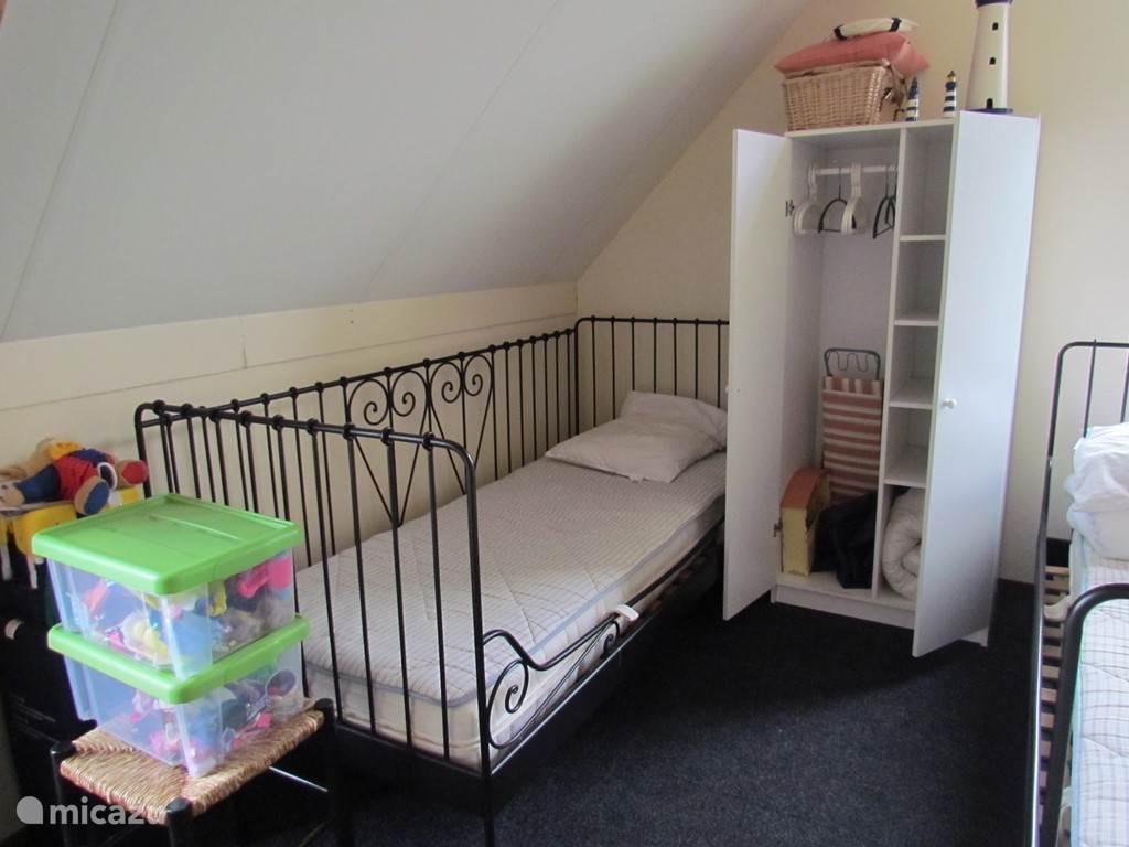 Slaapkamer III met twee eenpersoonsbedden en extra kinderbedje.