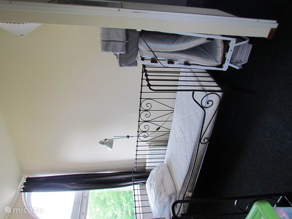 Lichte slaapkamer met twee éénpersoonsbedden. Extra opklapbed en extra kinderbedje aanwezig.