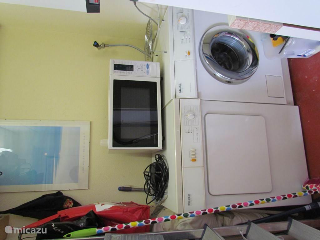 In de bijkeuken staan een wasmachine, droogtrommel en magnetron.