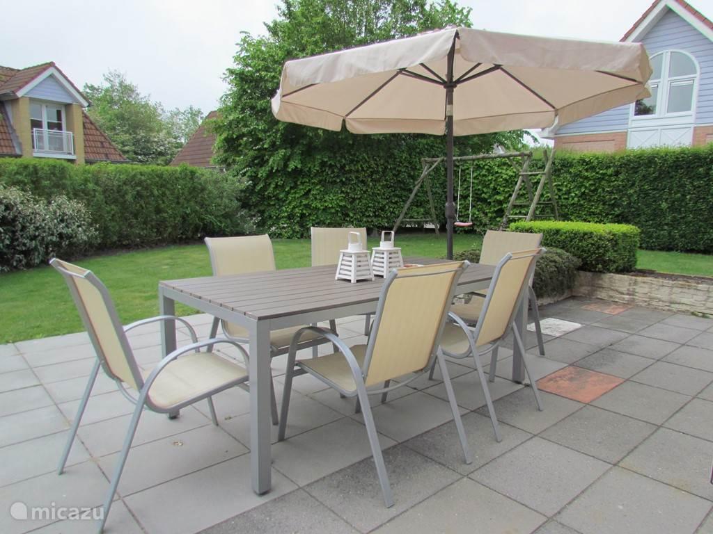 Vanuit openslaande deuren in de keuken stapt u zo op dit grote terras met tuintafel en 6 stoelen.