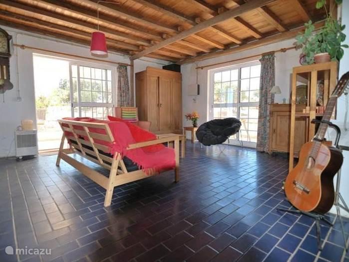 De heerlijke grote woonkamer - met muziekinstrumenten en uitzicht over de heuvels