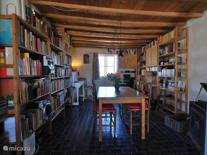 De eethoek met houtkachel, computer en uitgebreide bibliotheek