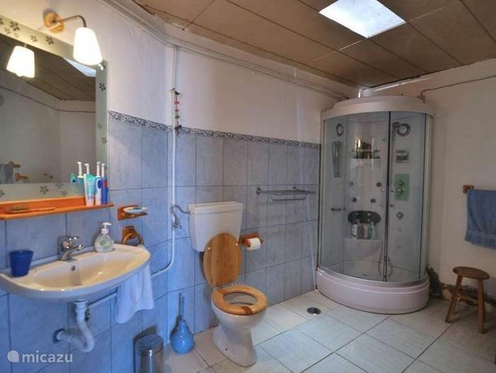 De tweede badkamer met douche, toilet en wastafel (deze wastafel heeft alleen koud water). Inmiddels met een mooi balkenplafond.