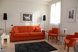De woonkamer met een stenen vloer en frisse meubilering. Rechts het raam aan de straatzijde. De bank is in een handomdraai een confortabel tweepersoons bed.