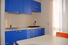 Een kijkje in de keuken, met 4-pits gasstel, een eethoek voor 5 personen, koelkast, magnetron, waterkoker, broodrooster en koffiezetapparaat.