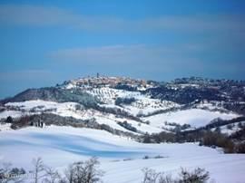 Radicondoli gezien vanuit de richting van Belforte. Zoals zoveel stadjes in Toscane is Radicondoli op een heuvel gebouwd. Heel vaag is de hoge toren van het gemeentehuis te zien.