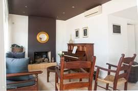Open haard en piano in de woonkamer (villa 1)