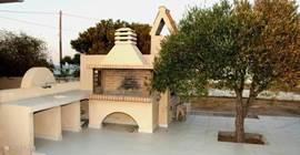 Achter het huis staat een grote stenen BBQ (villa 1)