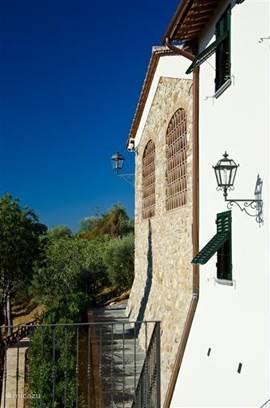 Links de ruwe buitenmuur met boogramen en daarvoor de originele gemetselde roosters van terracotta tegels. Authentiek in de regio en heel praktisch zonwerend.
