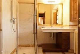 een der badkamers met royale douche, in marmer uitgevoerd.