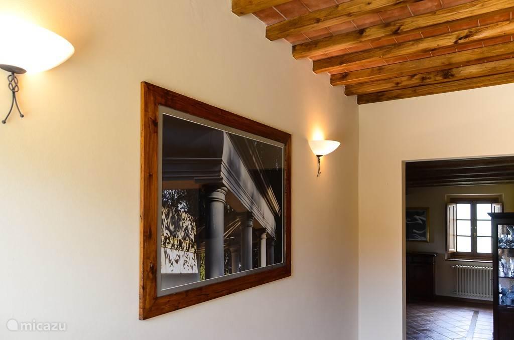 Foto's van kunstwerken op het landgoed decoreren de kamers. Hier de Toscaanse tempel in de Giardino Secreto van Villa Licia