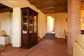 Kijkje naar de entreehal. Antieke glazenkast links.