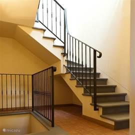 In grijze hardsteen en smeedijzer volgens de tradities uitgevoerde trap naar boven.