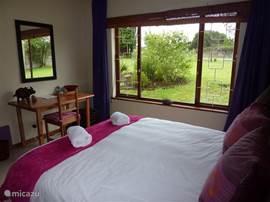De ruime paarse kamer met twee-persoonsbed.