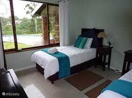 De blauwe kamer heeft twee een-persoonsbedden en een ruime inbouwkast.
