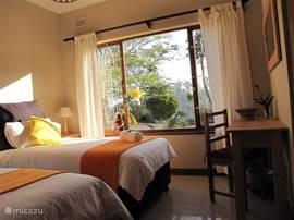 De gele kamer met twee een-persoonsbedden en een ruime inbouwkast.
