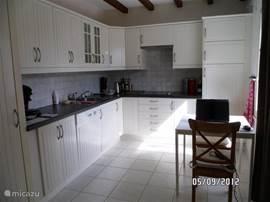 Complete open keuken met koelkast en vrieslade, magnetron, koffiezetapparaat en een aparte Senseo, een waterkoker en vaatwasser. De wasmachine staat in een aparte ruimte.