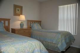 Twin slaapkamer met twee aparte bedden, inbouwkast en flatscreen t.v. aan de muur.