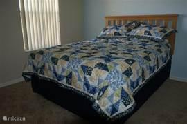 De queen slaapkamer met inbouwkast en flatscreen t.v.