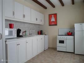 Keuken met veel bergruimte, magnetron, koffieapparaat en aparte Senseo, waterkoker en gasfornuis met oven en vaatwasser. De wasmachine staat in een aparte ruimte.