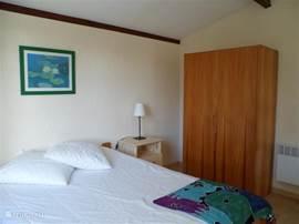 Ouderslaapkamer met nachtkastjes en linnenkast.