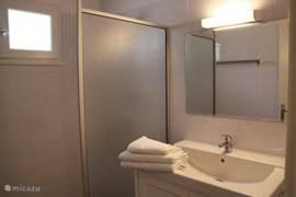 Badkamer met inloopdouche, wastafelmeubel en verwarmingselement.