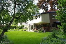 De achterzijde van de villa met een gedeelte van de prachtige tuin