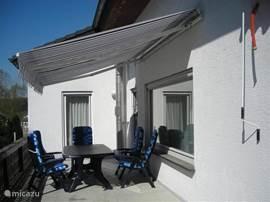 Terras op ruim balkon 1e verdieping, toegang vanuit eetkamer, 2 zonneschermen, tuinset
