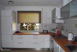 Een meer dan complete keuken met koelkast, oven, vaatwasmachine, magnetron, espressomachine etc.