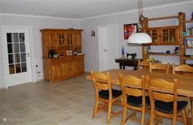 Eetkamer met zeer ruime eettafel voor 6-8 personen, toegang naar keuken en trap naar bovenverdieping en souterrain