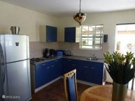 The kitchen in Caribbean blue with large fridge freezer