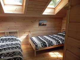 2 pers slaapkamer boven. 2 losse bedden van 200 x 90 cm. Bedden kunnen makkelijk naast elkaar worden gezet. Indien gewenst kan 1 van de bedden naar de overloop, dan wel kan een extra bed (zelf mee te nemen, bv. luchtbed) op de overloop worden geplaatst