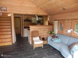 Woonkamer, met leistenen vloer en vloerverwarming, luxe open keuken, veel bergruimte onder de trap