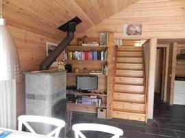 Woonkamer met spekstenen kachel, eethoek, boekenrek, stereo/tv en trap naar 1e verdieping