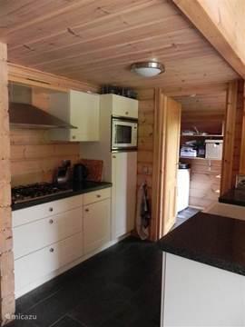 Open keuken, voorzien van 5 pits gasfornuis, grote koelkast, combimagnetron, vaatwasser en veel kastruimte. Deur naar bijkeuken, met wasmachine, vrieskast, verwarmingsketel en deur naar de tuin