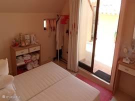 De slaapkamer op het dakterras. Als zonwering is een elektrisch rolluik aangebracht.