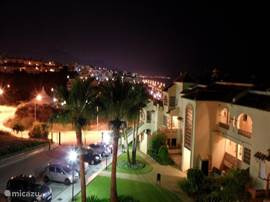 Avondopname vanaf de zijkant van het terras. De verlichting van het park en de lichtjes in de verte doen zeer gezellig aan.