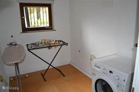Laundry room with washing machine and drying rack and ironing.