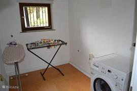 Wasruimte met wasmachine en droogrek en strijkplank met strijkijzer.