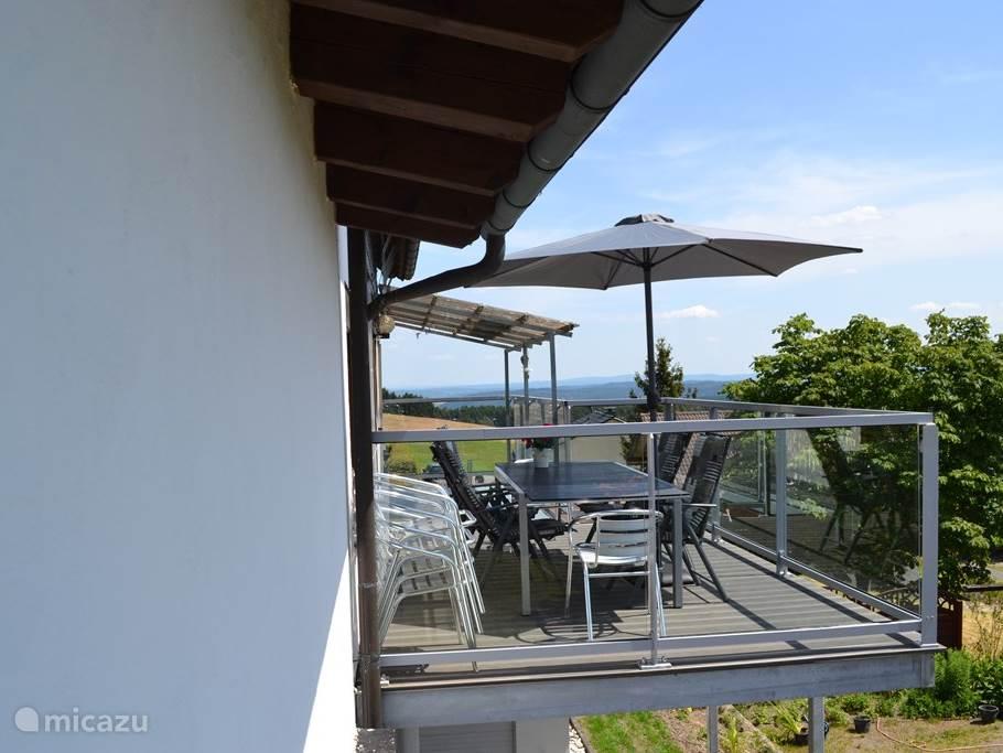 Achterkant woning met terras en nieuw balkon met tuinstoelen