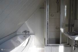 Upstairs bathroom with bath and shower and sink.