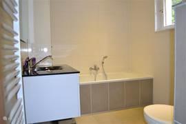 Badkamer begane grond met bad, wc en urinoir