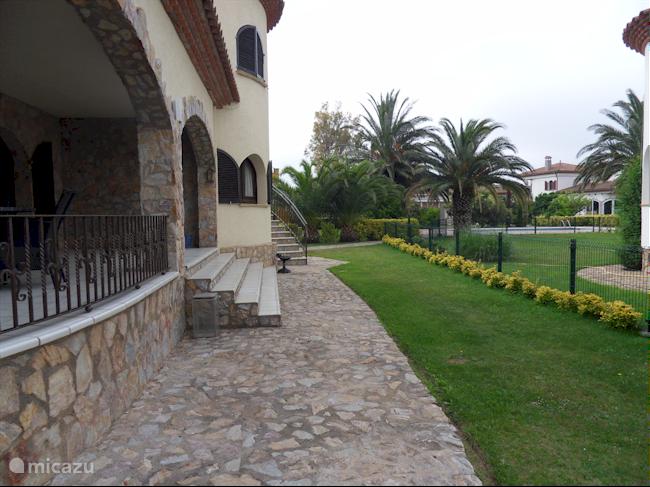 Ruime tuin met veranda en twee tafels en 8 stoelen en 4 ligbedden