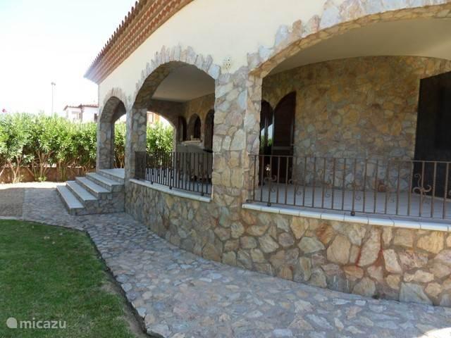 Ruime tuin met veranda en twee tafels en 8 stoelen