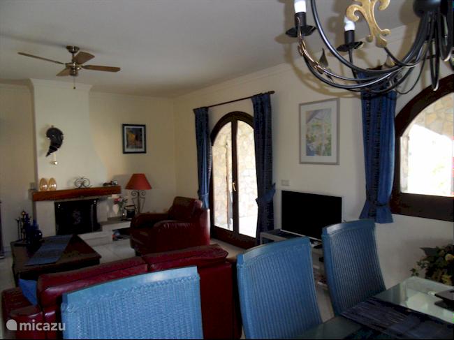 Ruime woonkamer met zithoek en open keuken.