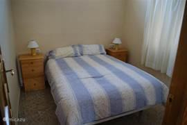 Tweede kamer met tweepersoonsbed en een kledingrek